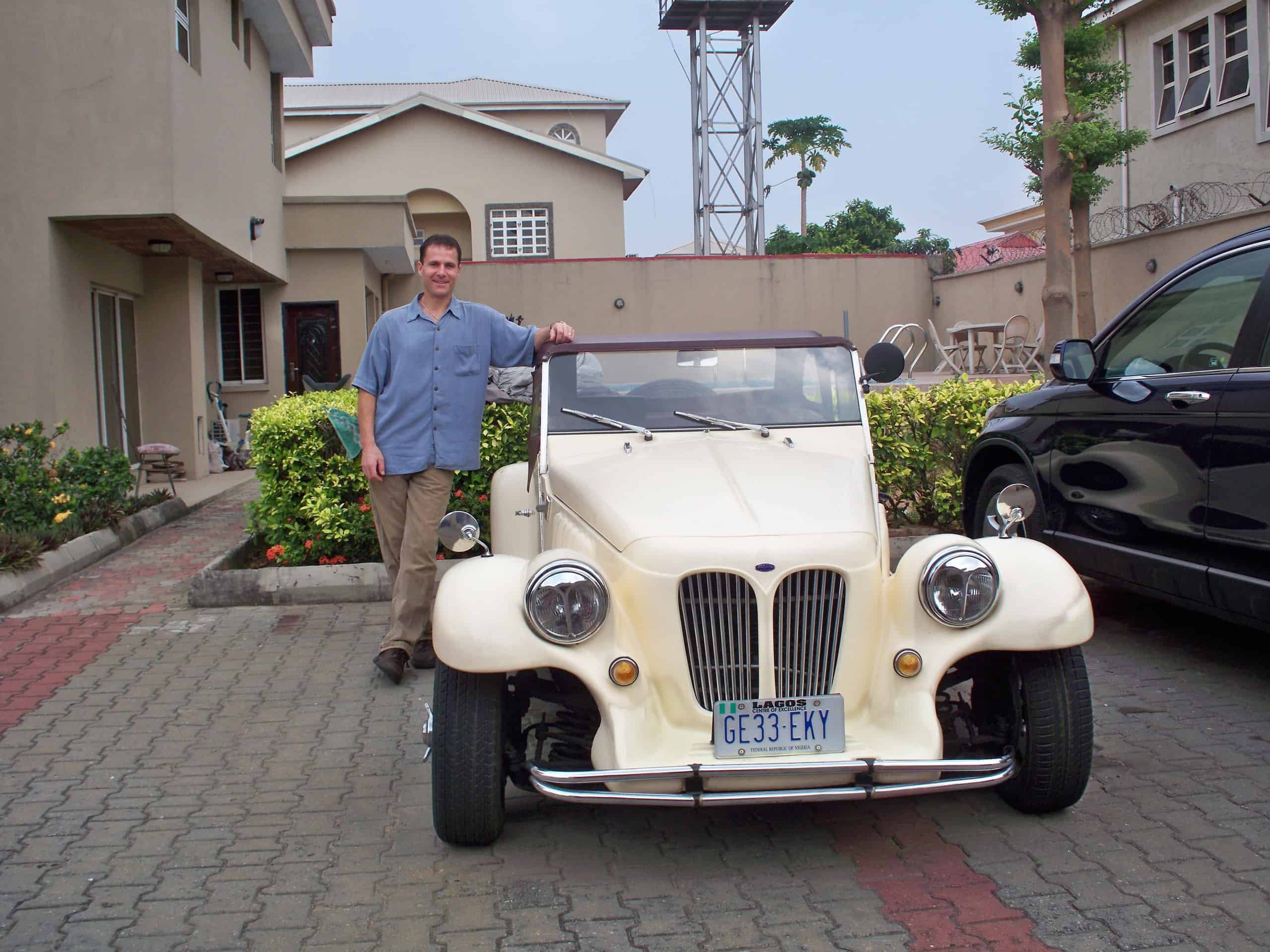 Steve Roller standing with a off white vintage car
