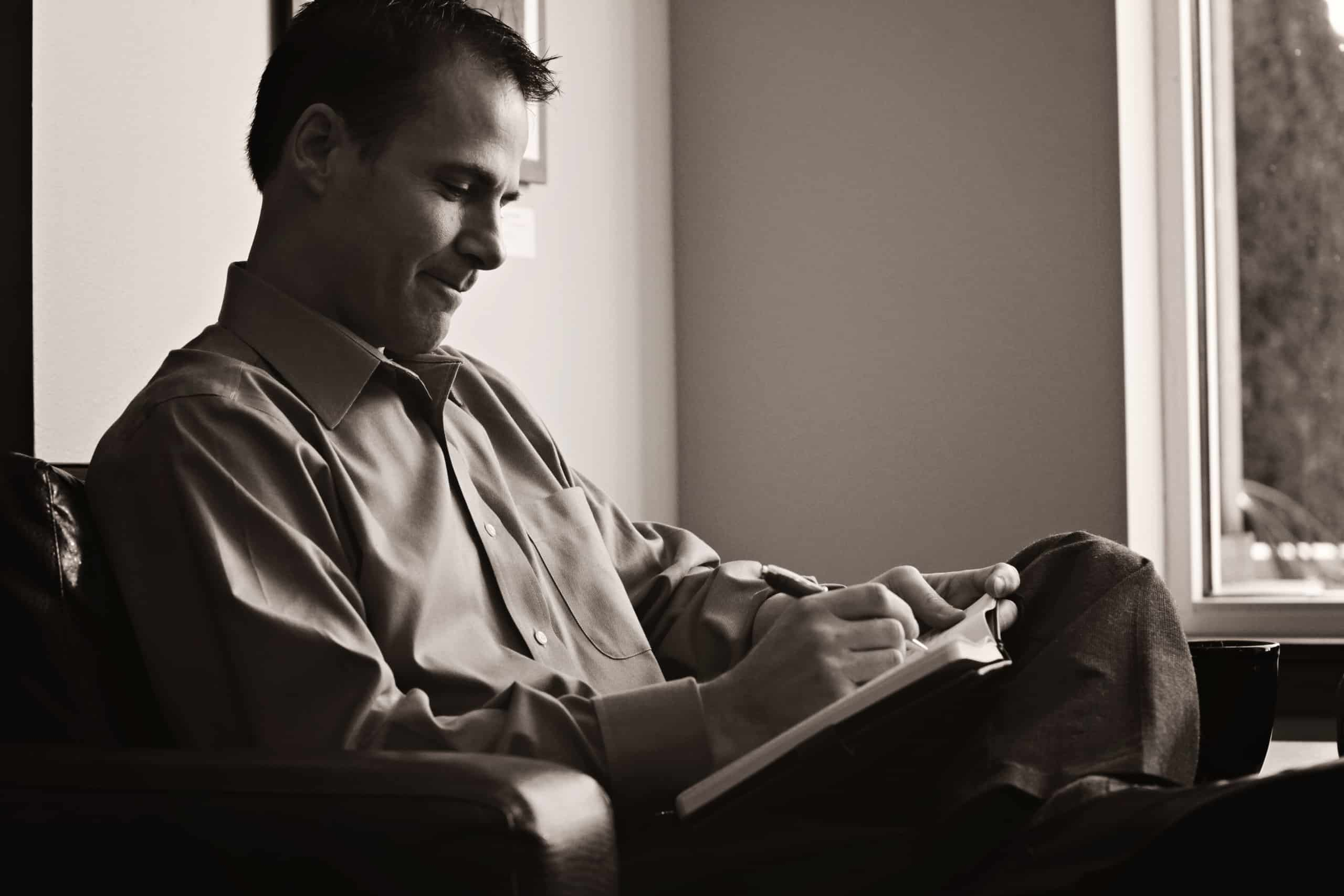 A black and white photo of Steve writing in a note book