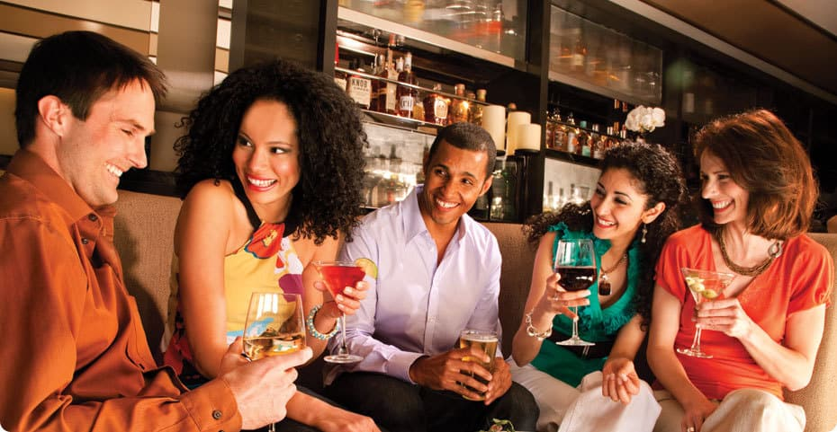 A group of people talking and enjoying drinks together in a bar