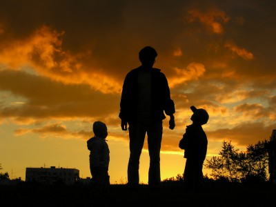A father playing outside at sunset with his two children