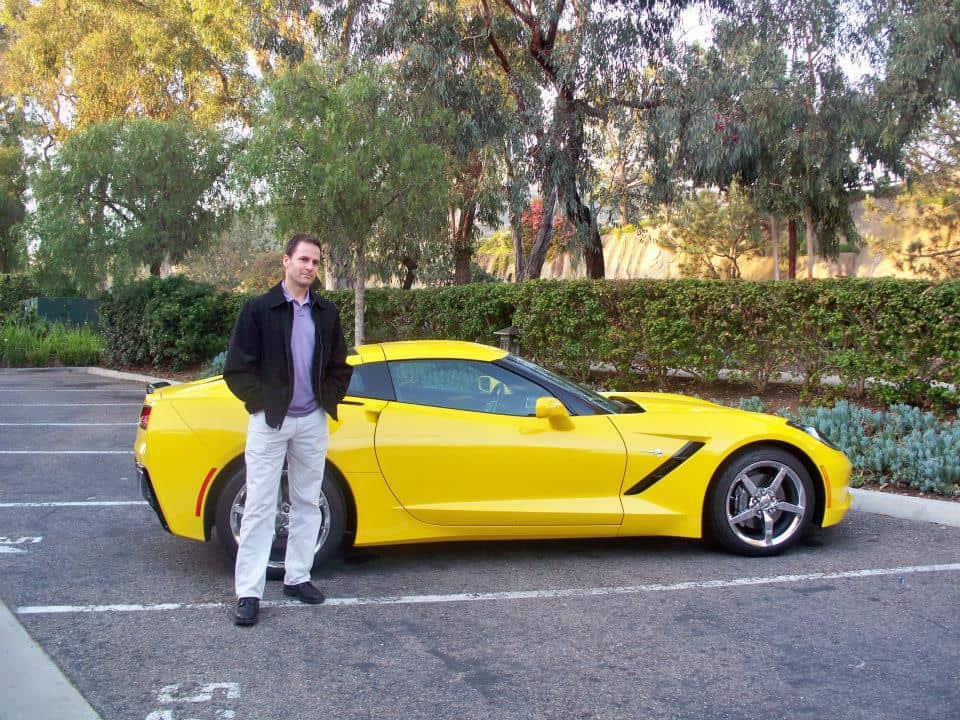 Steve standing next to a yellow sports car