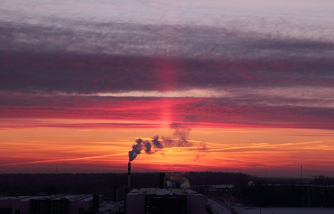 A view over a factory building at sunset with smoke coming out of a smoke stack