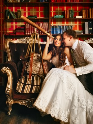 A bride and groom sitting on a sofa and looking out of a telescope
