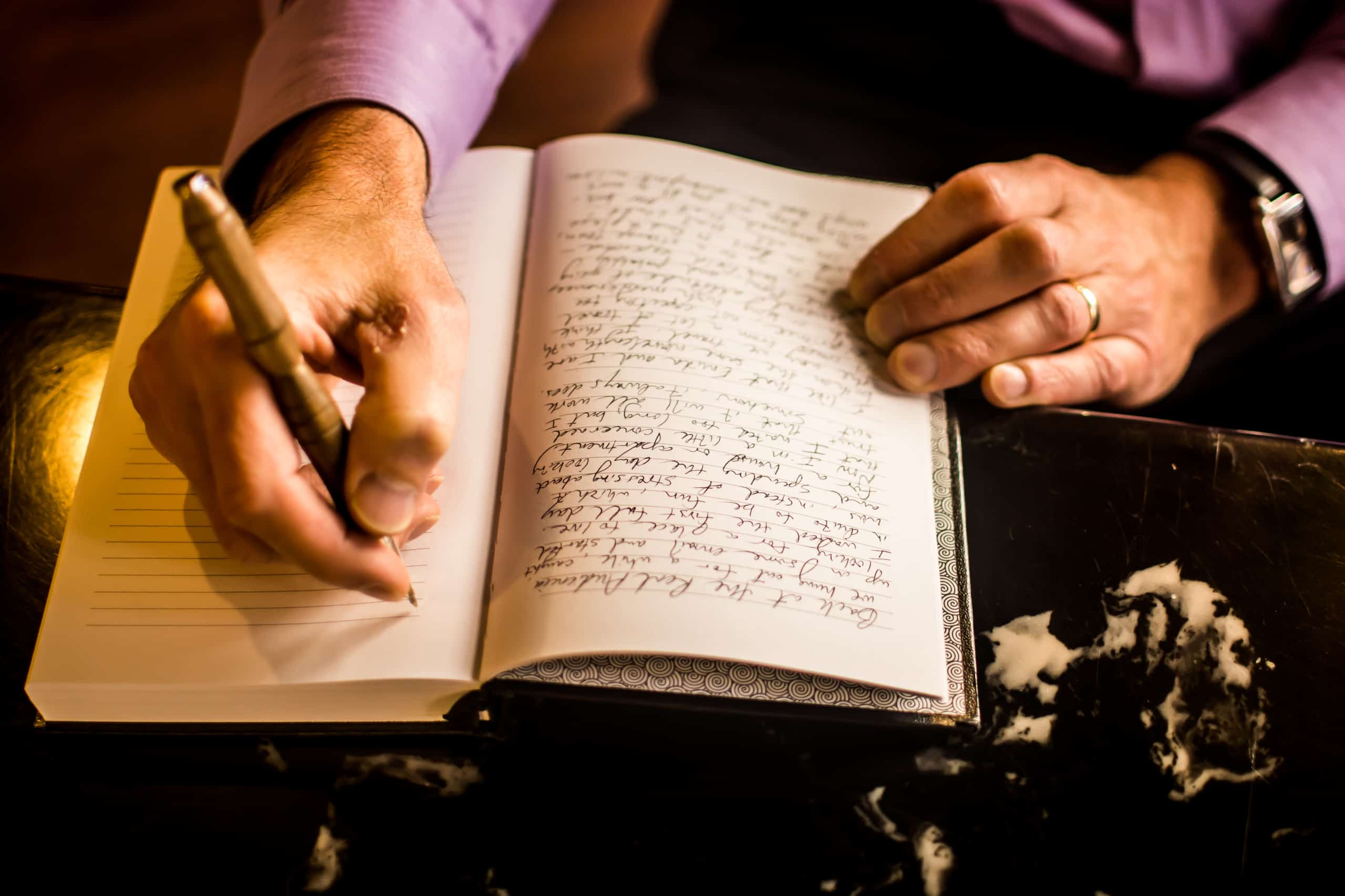 A person using a calligraphy pen to write in cursive in a book